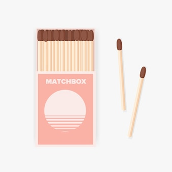 Matchbox of modern design and pair of wooden matches lying beside it isolated on white background.