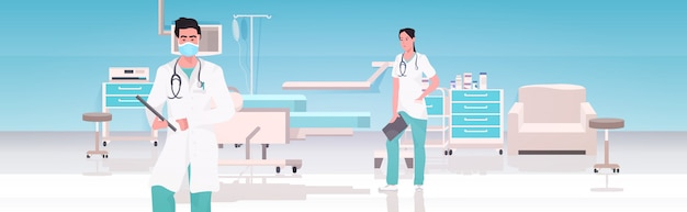 Medical doctors couple in uniform working together in operating room modern hospital clinic interior teamwork concept horizontal