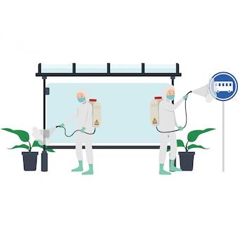 Медицинский персонал распыляет дезинфицирующее средство возле автобусной остановки