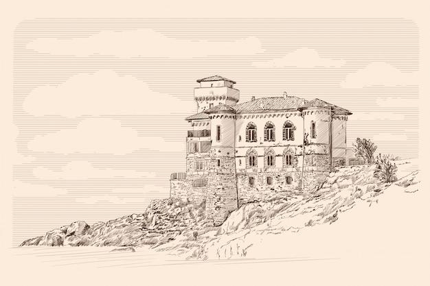 Средневековый каменный замок с башнями на скалах у моря.