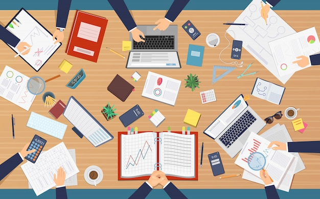 会議のトップビュー。コンピューターでラップトップの議題を書く書類を分析する紙の仕事を作るテーブルに座っているビジネスマンの専門家