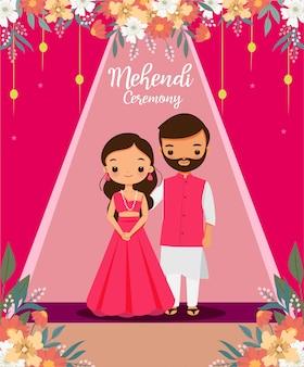 結婚式の日にmehendi式のピンクの伝統的なドレスでかわいいインドのカップル