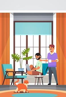 Мужчины вместе с ноутбуком пьют кофе, проводя время вместе во время карантина