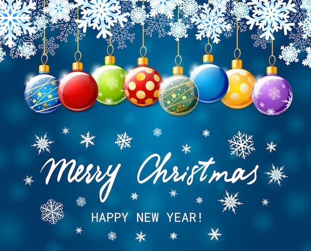 メリークリスマスと新年あけましておめでとうございますのバナー。カラフルなクリスマスボールと青い背景の上の紙の雪片との休日
