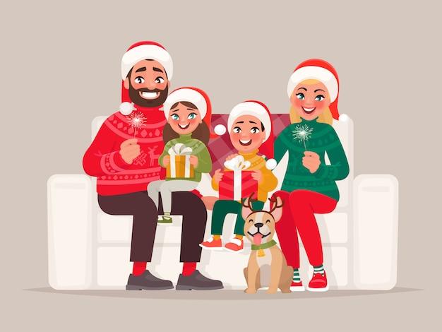 Веселого рождества и счастливого нового года. семья сидит на диване на фоне изолированной