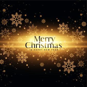 黄金の輝きと雪のメリークリスマスと幸せな新年のグリーティングカード
