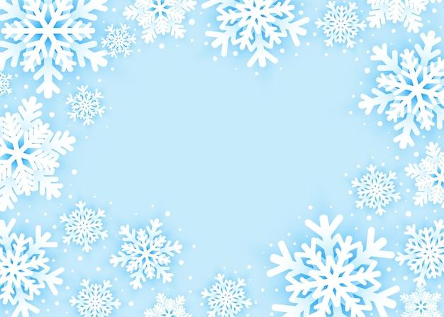 Поздравительная открытка с рождеством и новым годом со снежинками на синем фоне.