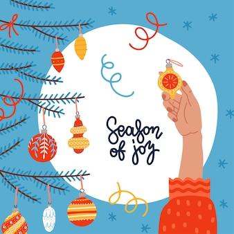 기쁜 성 탄과 새 해 복 많이 받으세요 인사말 카드 젊은 여성 손 장식 요소와 크리스마스 트리...