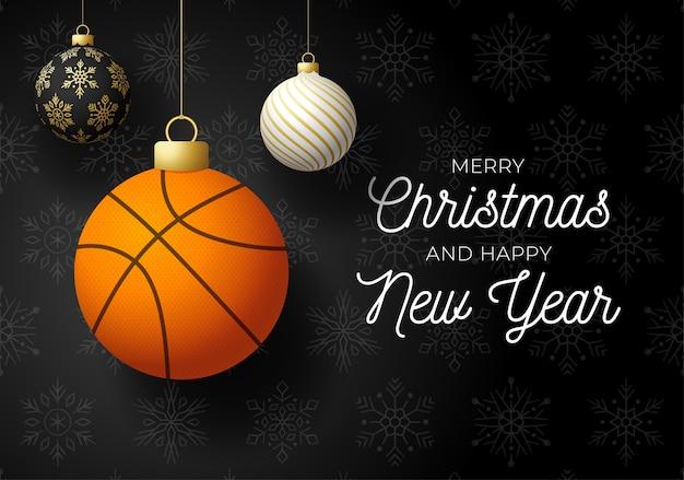 С рождеством и новым годом роскошная спортивная открытка. баскетбольный мяч как рождественский бал на черном фоне.