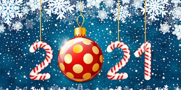 赤と白の渦巻きキャンディースタイルの2021年のメリークリスマスと新年あけましておめでとうございます。