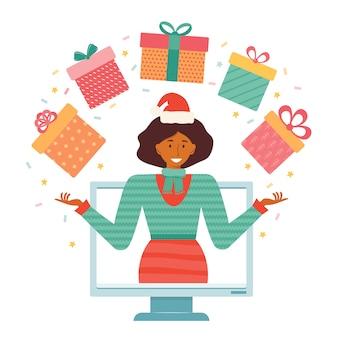 メリークリスマスと新年。サンタの帽子をかぶった女性は、コンピューターの背景でクリスマスマーケット、セール、割引、懸賞、プレゼント、当選者の賞品、ギフトを宣伝しています。オンラインショップでのホリデーセール