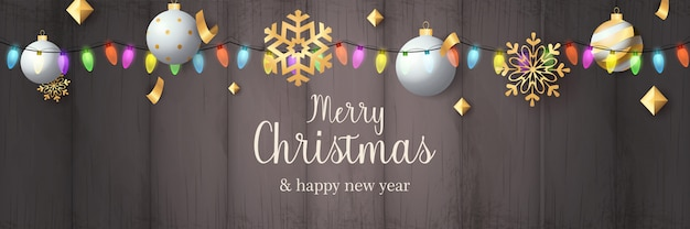 Merry christmas banner with balls on grey wooden ground
