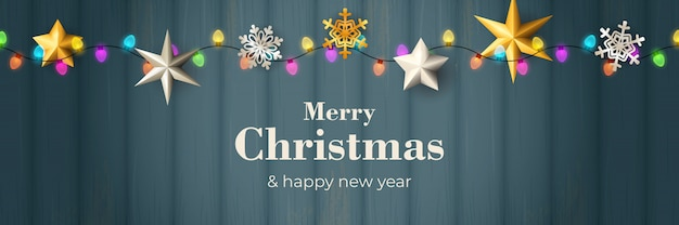 Merry christmas banner with garland on blue wooden ground