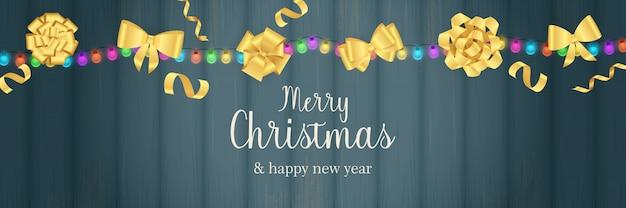 Merry christmas banner with gold bows on blue wooden ground