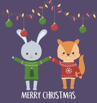 メリークリスマスのお祝いのかわいいウサギとリスとセーターとハンギングボールとライト