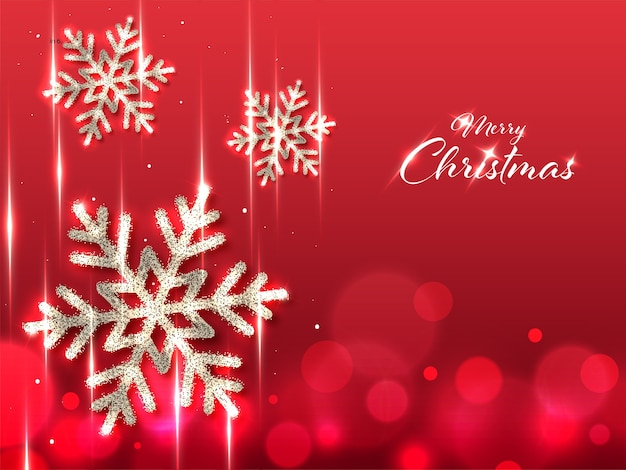 Merry christmas font with silver glittering snowflakes and lights effect on red background