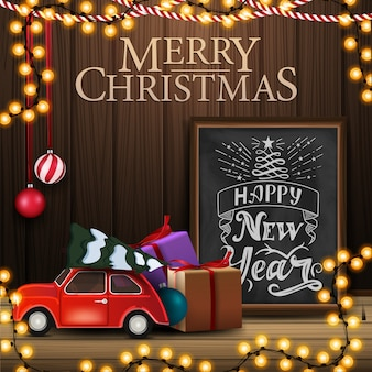 Merry christmas greeting card with vintage car carrying christmas tree, chalkboard with beautiful greeting lettering and wooden wall with christmas decor