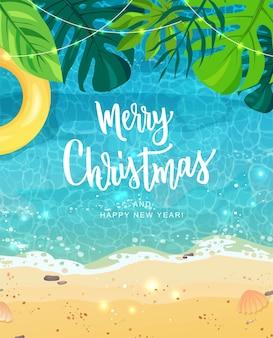 С рождеством христовым рука надписи для экзотического празднования нового года. летний берег моря, тропические листья.