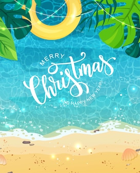 Merry christmas hand lettering text for exotic new year celebration. summer seashore with sand and yellow swim ring, tropical leaves, top view.