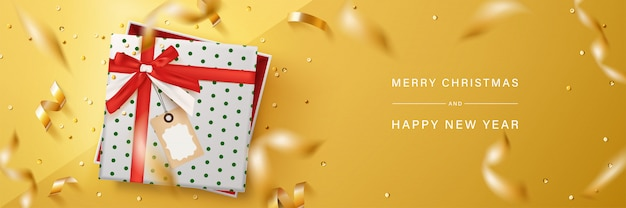 Merry christmas and happy new year banner design. gift boxes with gold flying ribbon on yellow