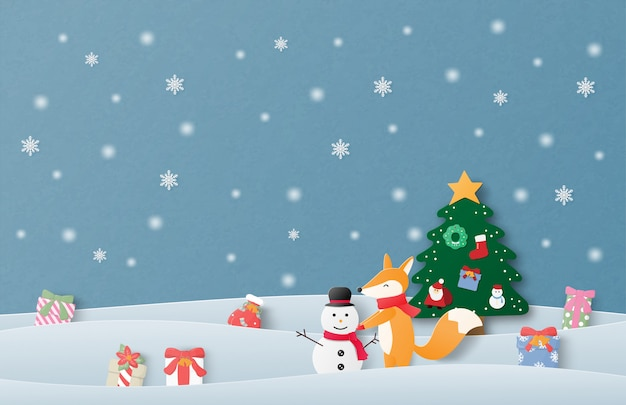 Merry christmas and happy new year greeting card in paper cut style. christmas celebration background with happy baby fox making snowman on snow field.