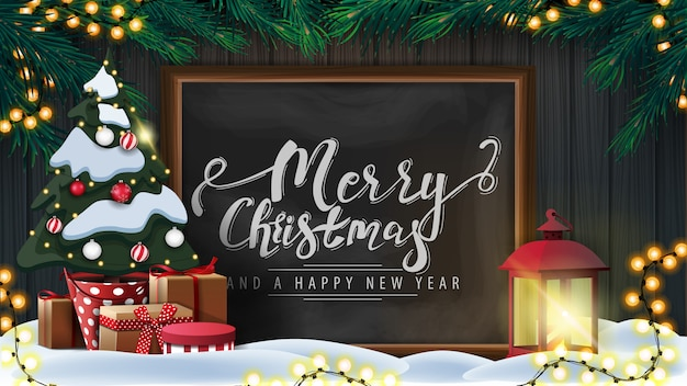 Merry christmas and happy new year with wooden wall, christmas tree branches, garland, chalk board with lettering, old lantern and christmas tree in a pot with gifts
