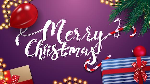 С рождеством, фиолетовая открытка с подарками, красный шар, гирлянда и ветки елки, вид сверху