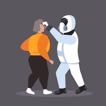 Человек в костюме хазмат, проверяющий температуру больной женщины, распространяющей эпидемию коронавирусной инфекции вирус mers-cov ухань 2019-нков концепция риска пандемии для здоровья полная длина