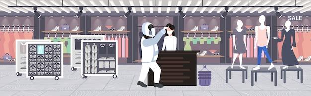Человек в костюме хазмат проверка температуры женщина продавец распространение коронавирусная инфекция эпидемия вируса mers-cov ухань 2019-нков концепция риска пандемии для здоровья полная длина горизонтальный