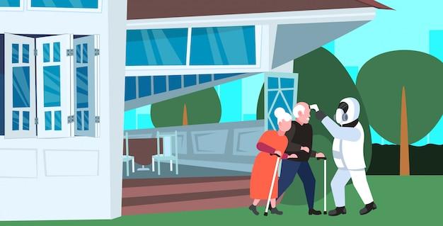 Специалист по костюму хазмат, проверяющий температуру старшего мужчины женщина пара эпидемия коронавирусной инфекции вирус mers-cov ухань 2019-нков концепция риска пандемии для здоровья полная длина горизонтальный