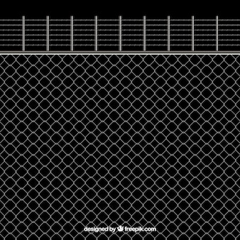 Metal fence with barbed wire on black background