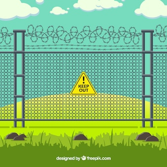 Metal fence with barbed wire in green landscape
