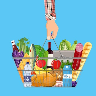 Metal shopping basket full of groceries products in hand.
