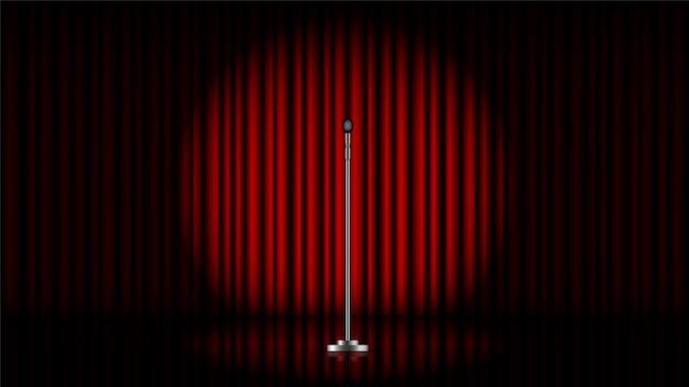 빨간 커튼과 스포트라이트가 있는 무대 위에 스탠드가 있는 마이크