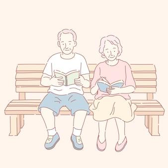 중간 나이 든 부부 독서 책과 공원 벤치에 앉아
