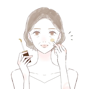 Middle-old woman applying concealer to face. on a white background.