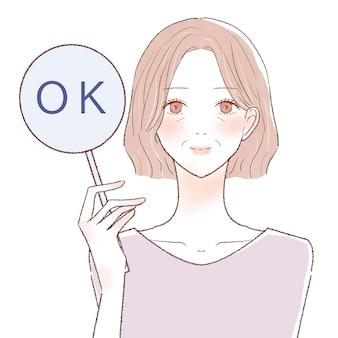 Okサインを刻む中年女性。白い背景に。