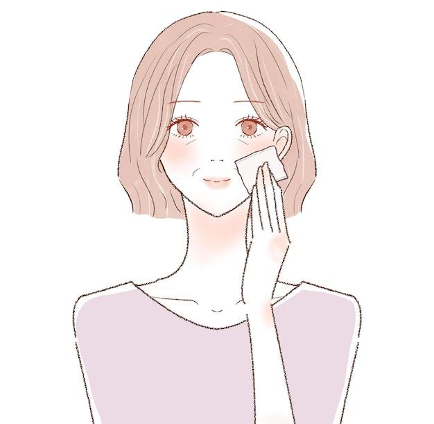 一枚の紙で顔の皮脂を取る中年の女性。白い背景に。