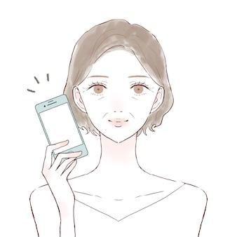 スマートフォンを持つ中年の女性。白い背景に。