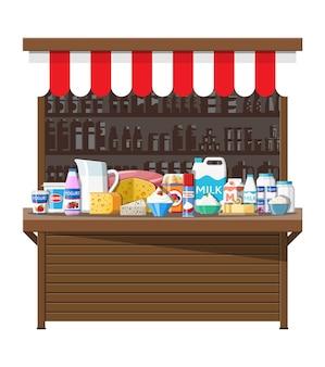 ミルクストリートマーケット店の屋台。ファーマーショップまたはショーケースカウンター。乳製品は食品のコレクションを設定します。ミルクチーズヨーグルトバターサワークリームクロテッドクリーム農産物。ベクトルイラストフラットスタイル