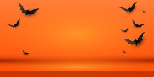 黒い紙コウモリの群れと最小限の創造的なオレンジ色の背景レイアウトデザイン。コピースペース付き