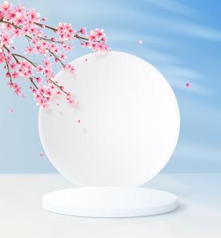 円筒形の空の台座と丸い壁のミニマルな背景。装飾的なピンクの花と青い空の製品展示プラットフォーム。