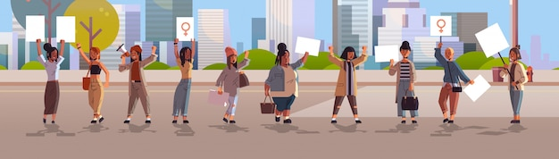 Mix race activists holding placards with female gender sign feminist demonstration girl power movement rights protection women empowerment concept cityscape background horizontal full length