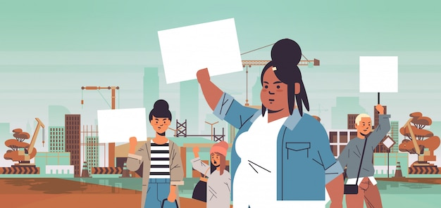 Mix race activists holding placards with female gender sign feminist demonstration girl power movement rights protection women empowerment concept portrait construction site background horizontal