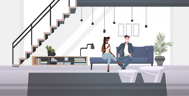 Mix race businesspeople couple sitting on couch discussing during meeting