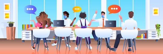 マスクを着た混血のビジネスマンチームが、チャットバブルコミュニケーションのブレーンストーミングコロナウイルス検疫コンセプトの水平方向の全長図を会議中に話し合う