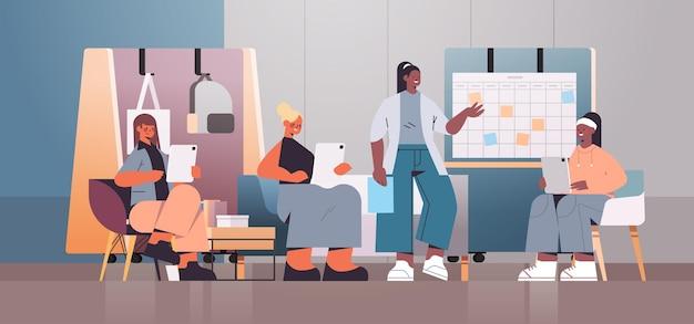 Бизнесмены смешанной расы работают и обсуждают во время встречи в концепции совместной работы в центре коворкинга