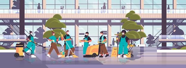 Смешайте гоночные чистящие средства в масках, дезинфицирующих клетки коронавируса, чтобы предотвратить пандемию covid-19, уборка, концепция дезинфекции, здание больницы, экстерьер, горизонтальное