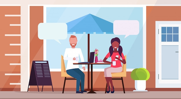Mix race couple sitting cafe table chat bubble communication concept street restaurant terrace outdoor cafeteria exterior flat horizontal full length
