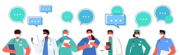 코로나 바이러스 전염병 채팅 거품 통신 개념 의료 노동자 팀 서 함께 세로 수평 벡터 일러스트 레이 션을 방지하기 위해 마스크를 착용하는 유니폼에 인종 의사를 혼합